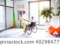 Young woman physiotherapist working with a senior man in wheelchair. 40298477