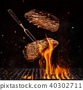 Flying beef steaks over grill grid 40302711
