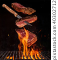 Flying pieces of beef steaks from grill grid 40302712