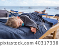 kid sleeping on deckchairs at the beach 40317338