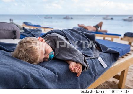 kid sleeping on deckchairs at the beach 40317338
