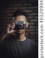 Asian Man Taking Picture With Vintage Camera on Brick Wall  40320994