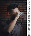 Asian Man Taking Picture With Vintage Camera on Brick Wall  40320997