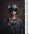 Asian Man Holding Vintage Camera Wearing Retro Helmet on Brick  40321001