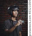 Asian Man Holding Vintage Camera Wearing Retro Helmet on Wall Br 40321004