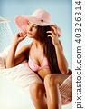 Beautiful woman in bikini relaxing in a hammock 40326314