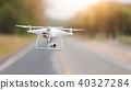 Drone copter flying with digital camera in park 40327284