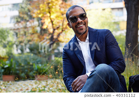 Portrait of Happy confident young African-American businessman in formal wear and sunglasses sitting 40331112