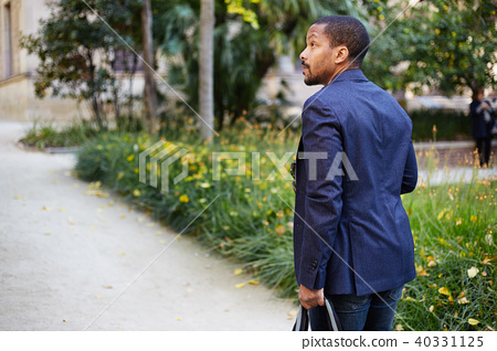 Portrait of Happy confident young African-American businessman in formal wear walking at city park 40331125