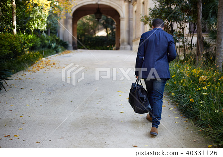 Portrait of Happy confident young African-American businessman in formal wear walking at city park 40331126