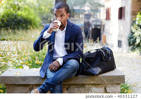 Portrait of smiling confident young African-American businessman in formal wear sitting at bench in 40331127
