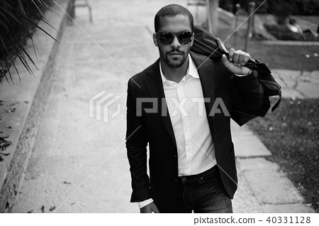 Portrait of Happy confident young African-American businessman in formal wear walking with 40331128