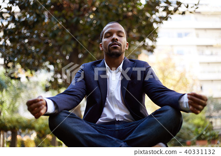 Young american african businessman in informal clothes meditating in lotus pose taking a deep breath 40331132