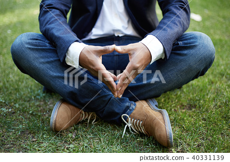 Young american african businessman in formal wear meditating in lotus pose taking a deep breath 40331139