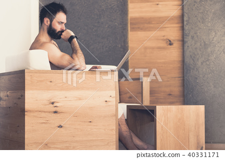 Handsome bearded man using laptop computer while resting in spa hotel. Man relaxing after hard day 40331171