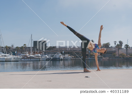 Fitness woman doing yoga urban practice outdoors. Healthy young girl practising yoga on seaside 40331189