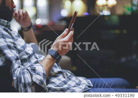 Handsome bearded man using electronic reader book computer while resting in lobby hotel. Man using 40331190