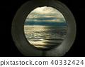Ship window or porthole view with a relaxing seascape and dark grey clouds 40332424