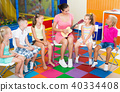 Happy children listening teacher playing small guitar 40334408