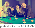 Group of adults playing pool. 40334592