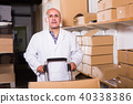Positive mature man worker standing with cart 40338386