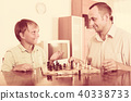 Man and teenager son playing chess. 40338733