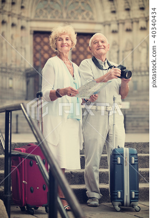 Senior man photographing sights while his wife looking map near old cathedral 40340434