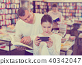 Father trying to draw daughter attention to book while she carried away with phone 40342047