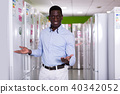 Smiling male standing near refrigerator in store of appliances 40342052