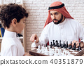 Arabian bearded father and little son play chess. 40351879