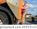Garbage removal worker riding on the back of the disposal vehicle 40354114
