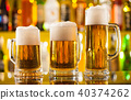 Jugs of beer served on bar counter 40374262