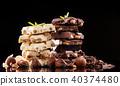 Pile of hazelnut chocolate on black background 40374480