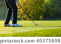 Close-up of man playing golf on green course 40375608