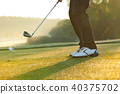 Close-up of man playing golf on green course 40375702