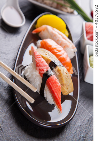 Delicious sushi pieces served on black stone 40376582