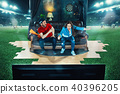 Ardent fans are sitting on the sofa and watching TV in the middle of a football field. 40396205