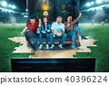 Ardent fans are sitting on the sofa and watching TV in the middle of a football field. 40396224