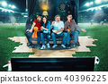 Ardent fans are sitting on the sofa and watching TV in the middle of a football field. 40396225