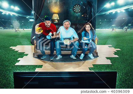 Ardent fans are sitting on the sofa and watching TV in the middle of a football field. 40396309