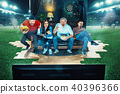 Ardent fans are sitting on the sofa and watching TV in the middle of a football field. 40396366