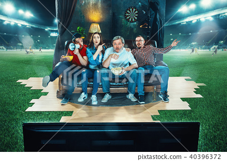 Ardent fans are sitting on the sofa and watching TV in the middle of a football field. 40396372