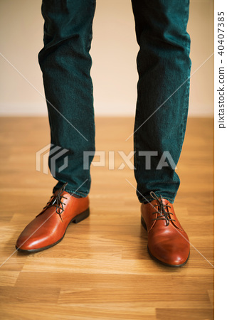 Man wearing shoes on wooden floor. Clothing 40407385