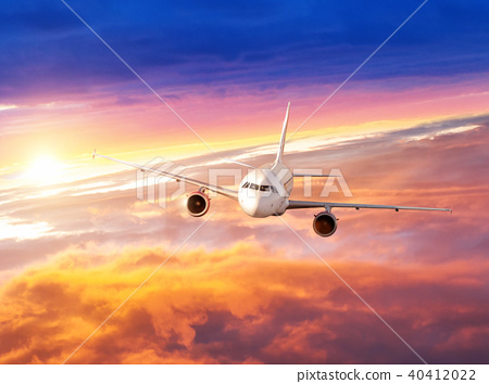 Airplane flying above clouds in dramatic sunset 40412022