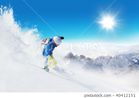 Skier on piste running downhill 40412151