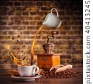 Splashing liquid of coffee into white cup on wooden table 40413245