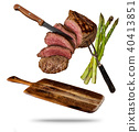 Flying beef steaks with grilled asparagus served on wooden cutting board. 40413851