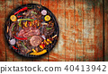 Top view of fresh meat and vegetable on grill placed on wooden planks 40413942