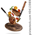 Flying beef steaks with grilled vegetable served on wooden cutting board. 40413989