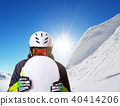 Snowboarder holding his snowboard off piste 40414206
